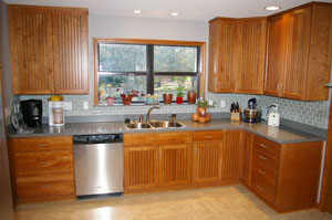 HomeCrest Bayport cherry cabinetry with corian countertops, glass tile backsplash.